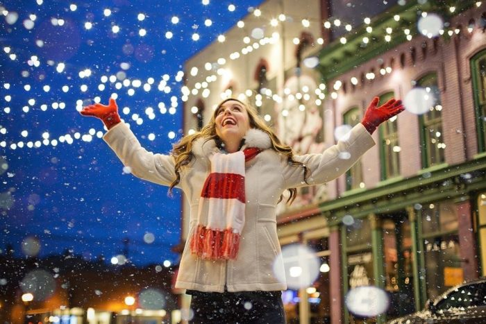 woman looking up and smiling as snow falls