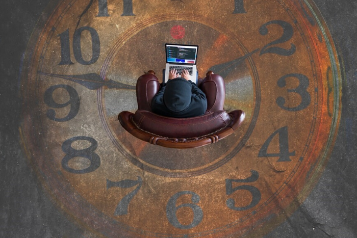 high shot looking down in a leather chair typing with a clock design on floor